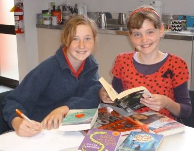 Two of the founding members of the Buller Book Buddies, Tara and Hayley, with some of their favourite books. The club is open to all library members aged between 8-12 who are prepared to commit half an hour once a month to share their favourite reads with others